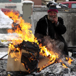 A homeless man warms up by burning cardboxes near the city hospital in Skopje